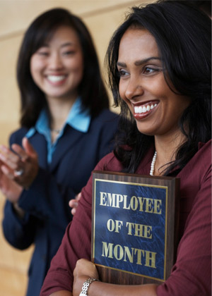 Woman holding employee of the month plaque